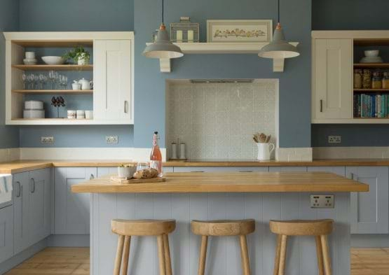 Laura Ashley Whitby kitchen with two tone painted cabinets in blue and white with island and wooden worktops