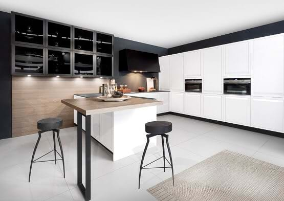 Rotpunkt Kitchen with white cabinets and contrasting matt black accessories and wooden breakfast bar