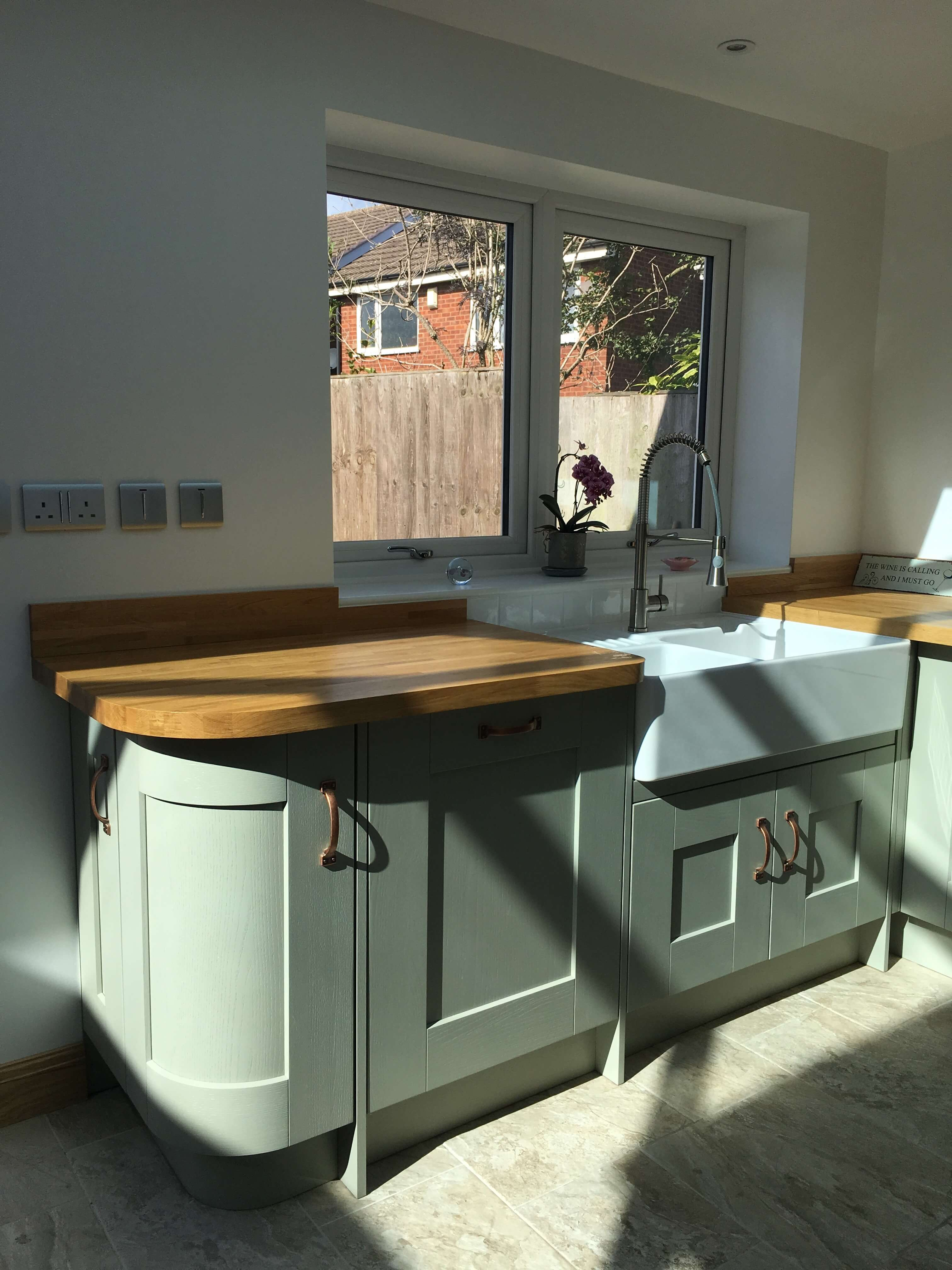 Austin kitchen in sage green with copper handles and Belfast sink