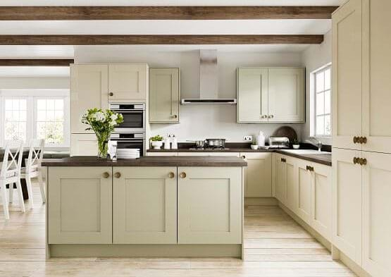 Casa Cranbrook in sage and stone. Traditional kitchen with two tone cabinets with feature island in sage green finished with walnut worktops and handles