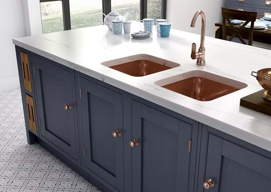 Laura Ashley Helmsley kitchen in navy blue colour scheme with cooper taps, sink and handles and statement floor tiles.
