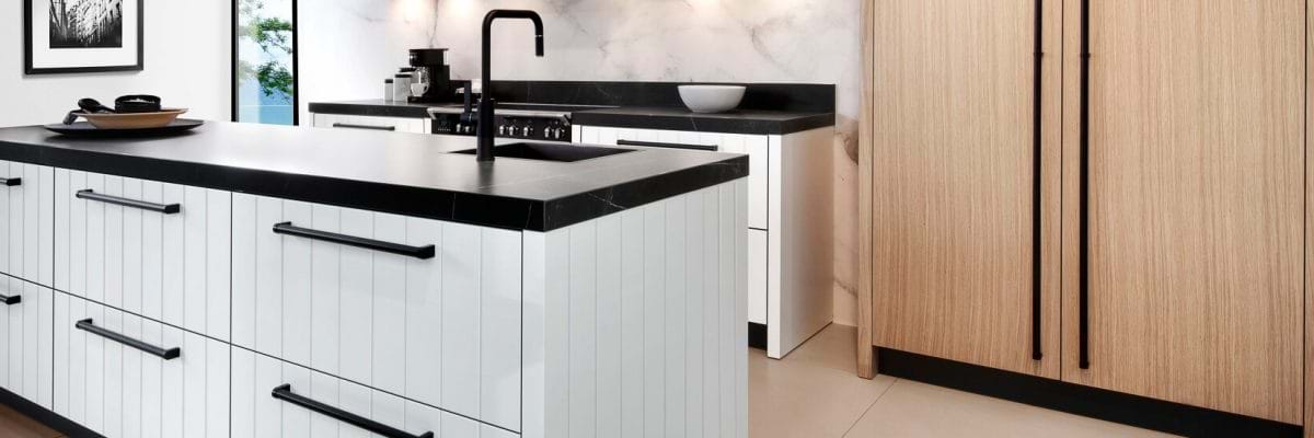 White painted kitchen with black handles, worktop and tap.