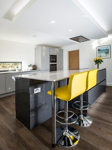 Rotpunkt linear kitchen in gloss finish with feature island in dark colour scheme with breakfast bar and seating