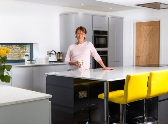 Fitted kitchen in grey and white colour scheme with feature island in grey gloss finish with breakfast bar