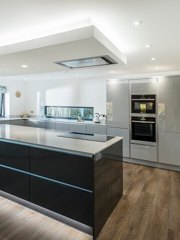 Gloss kitchen complete with handleless cabinets in grey and white colour scheme