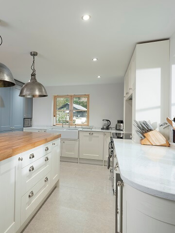 Casa Ashbourne kitchen in white colour scheme with two tone worktops in light stone and dark wood.