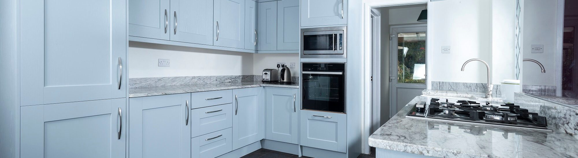 Casa Ashbourne in light blue colour scheme with stone worktop and integrated appliances