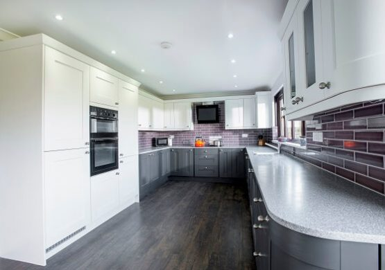 Casa Ashbourne in grey and white colour scheme with curved worktop and feature splash back