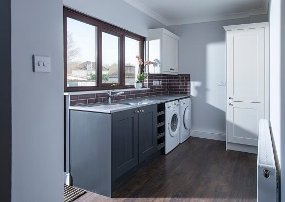Casa Ashbourne utility room with two tone cabinets in grey and white with sink, white goods and built in wine rack.