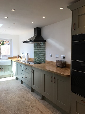 Painted kitchen in green colour scheme with wood worktops