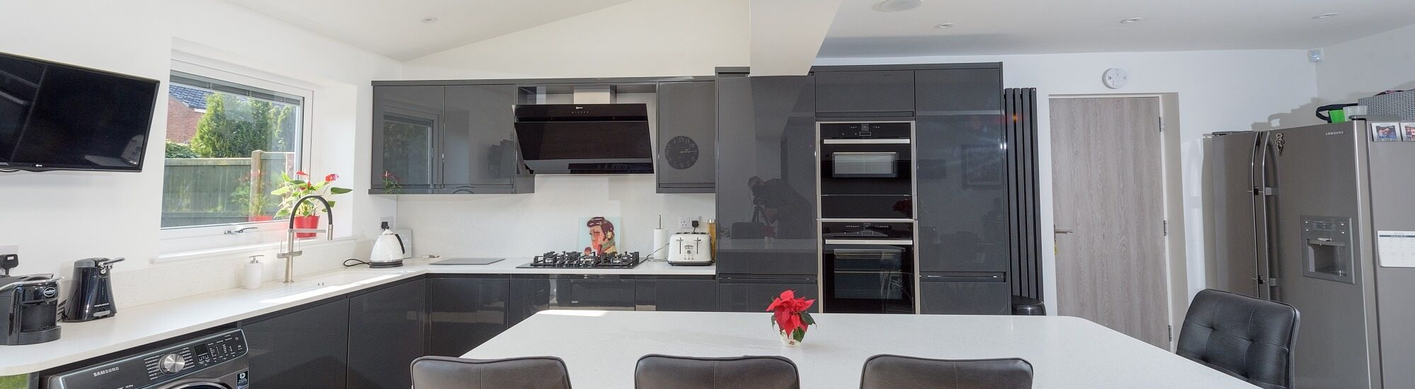 Rotpunkt gloss kitchen in white a grey colour scheme with built in induction hob and oven.